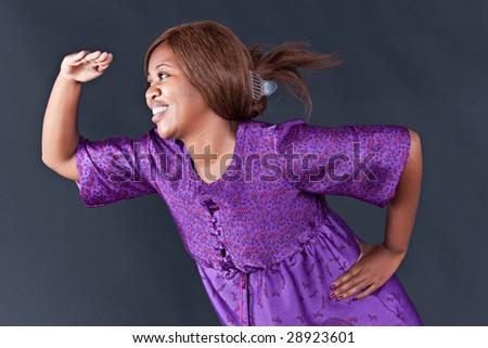 african girl gazing around , isolated on dark background - stock photo