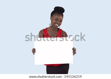 African girl holding a blank sign against a blue background - stock photo