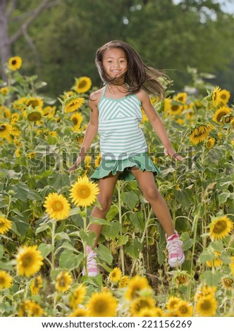 African girl jumping in flower patch - stock photo