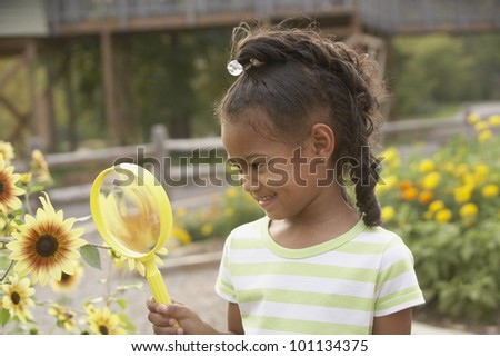 African girl looking at flower through magnifying glass - stock photo