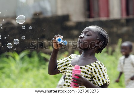African Girl Playing with Soap Bubbles Outdoors in Bamako, Mali. Black young beautiful girl having fun outdoors blowing soap bubbles. Happiness symbol. Elementary student happy outside her school. - stock photo