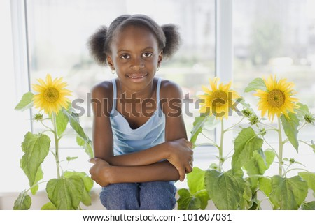 African girl sitting next to flowers - stock photo