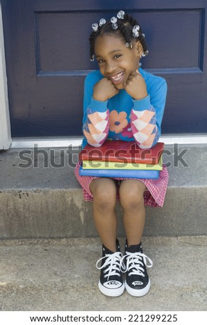 African girl sitting with school books - stock photo