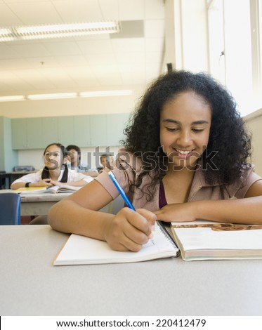 African girl smiling and working at desk in classroom - stock photo