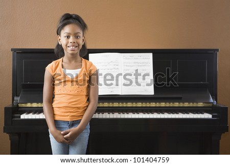 African girl standing in front on piano - stock photo