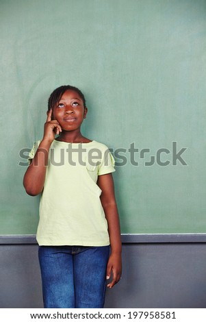 African girl thinking in elementary school in front of an empty chalkboard - stock photo