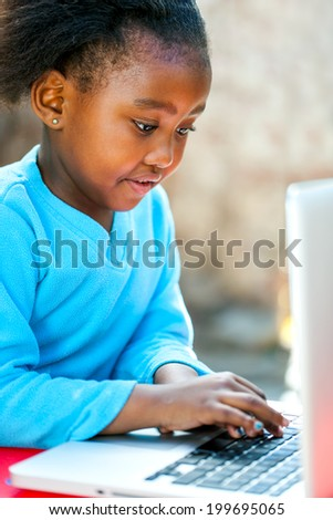 African girl typing and navigating on laptop outdoors. - stock photo