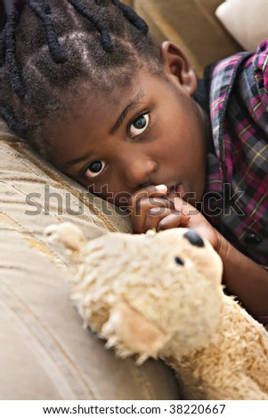 African girl with plaits resting on the couch with her old and very worn friend, the teddy bear - stock photo