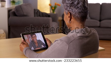 African grandma video chatting on tablet - stock photo