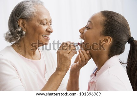 African grandmother helping granddaughter apply lipstick - stock photo