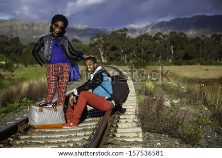 african guy and girl waiting for train on the tracks - stock photo