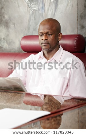 African guy reading newspaper while sitting at table on red leather sofa - stock photo