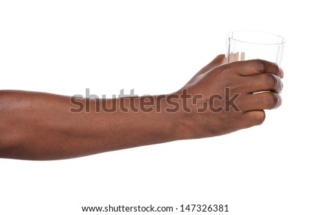 African hand holding out a clear glass of water.