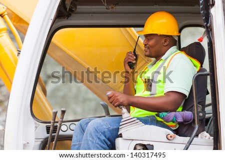 african industrial worker operating bulldozer while talking on walkie-talkie - stock photo