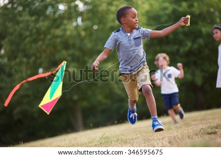 African kid having fun flying a kite in the nature  - stock photo