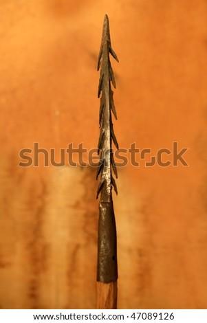 African lance weapon iron arrowhead in orange background - stock photo