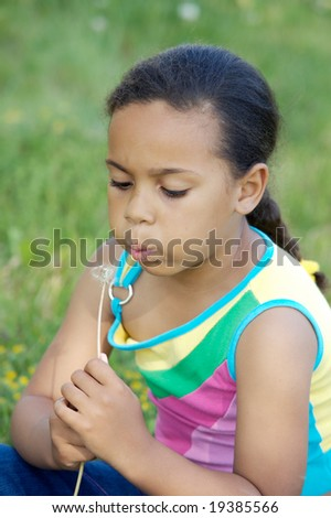 African little girl blowing one dandelion sitting on the field - stock photo