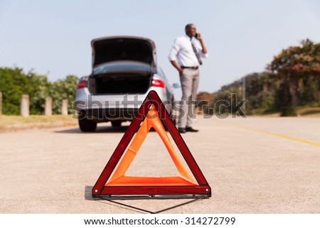 african male driver calling for help after car broke-down by the side of the road - stock photo