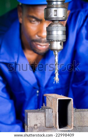 african male machinist working on industrial drilling machine in workshop
