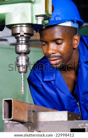 african male machinist working on industrial drilling machine in workshop - stock photo