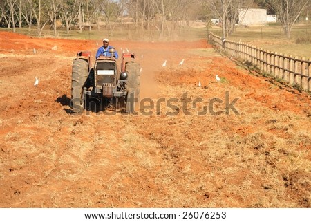 African male on a tractor tilling soil - stock photo