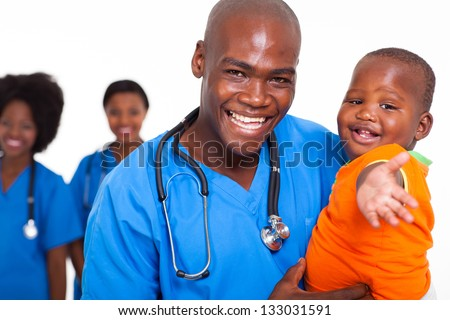 african male pediatric doctor playing with baby boy, and colleagues on background - stock photo