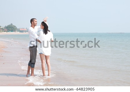 african man and asian woman lover on the beach - stock photo