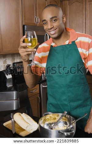 African man cooking and drinking wine - stock photo