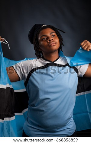 African man from Botswana with a flag smiling in a photo studio against a dark background happy
