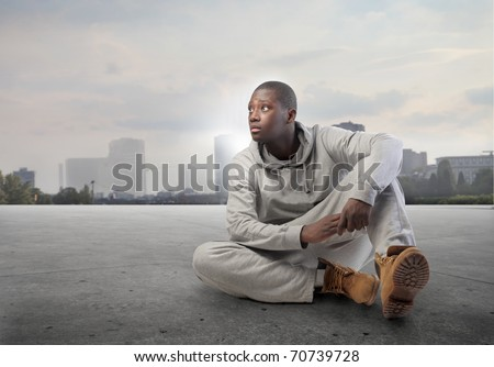 African man sitting on a city street with cityscape on the background - stock photo