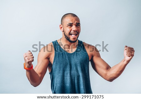 African man smiling happy victory, hands it upwards with his fists. On a gray background.