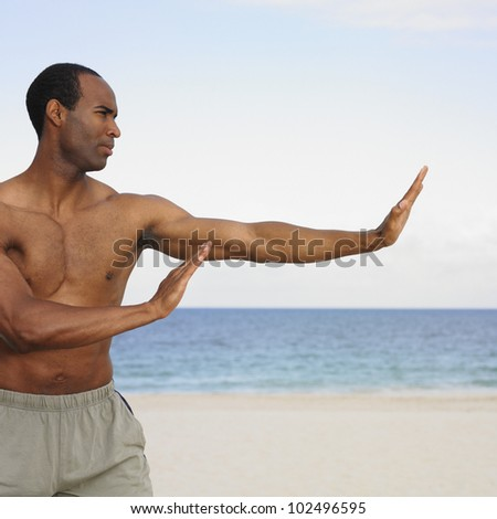 African man stretching on beach