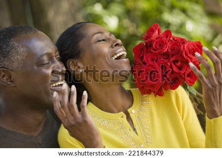 African man surprising wife with flowers - stock photo