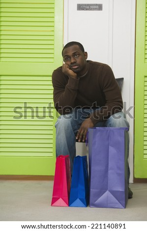 African man waiting outside dressing rooms - stock photo