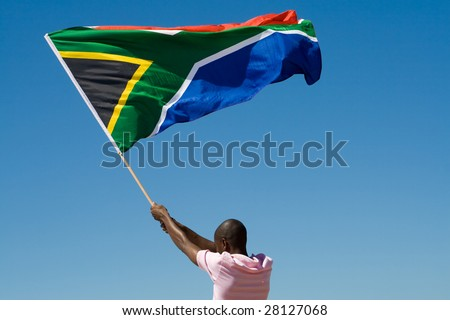 african man waving a south african flag against blue sky - stock photo