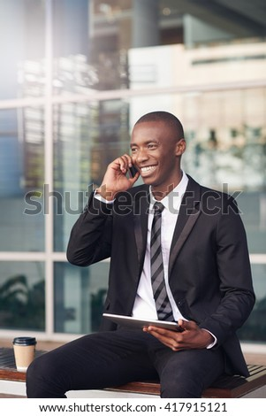 African man with a friendly smile talking on his phone - stock photo