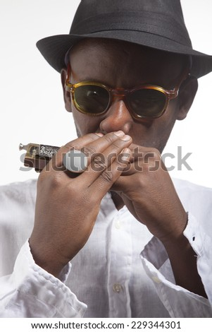 african man with glasses and hat play an harmonica