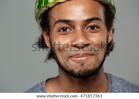African man with watermelon on head fooling over grey background.