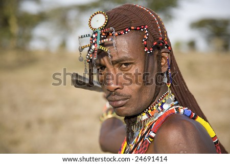 African Masai Warrior dressed in his traditional clothing. He is in the Masai Mara National Park wearing home-made Masai jewelry and his earlobes are stretched as is tradition with the Masai. - stock photo