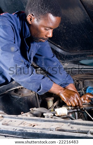 african mechanic working on a broken down vehicle - stock photo