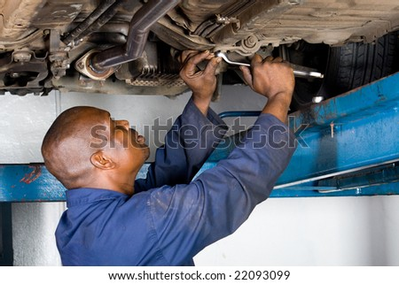 african mechanic working on a vehicle - stock photo