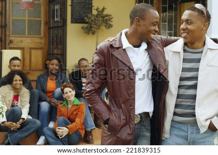 African men hugging with friends in background - stock photo