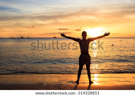 African  men raising arms up  at Sunset in Tarrafal beach in Santiago island in Cape Verde - Cabo Verde - stock photo