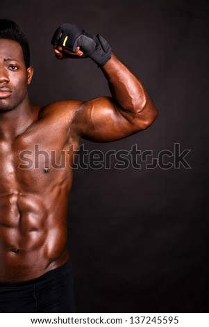 African model flexing his biceps, copy space area on the image.