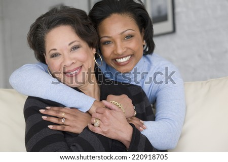 African mother and adult daughter hugging - stock photo