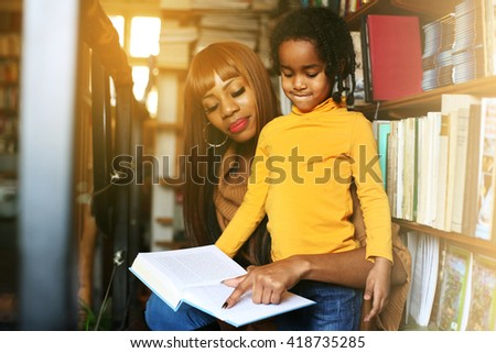 African mother and daughter reading together in library. Focus on little girl.  - stock photo