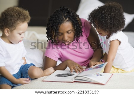 African mother reading to children - stock photo