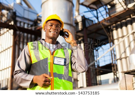 african oil and chemical worker talking on cell phone - stock photo