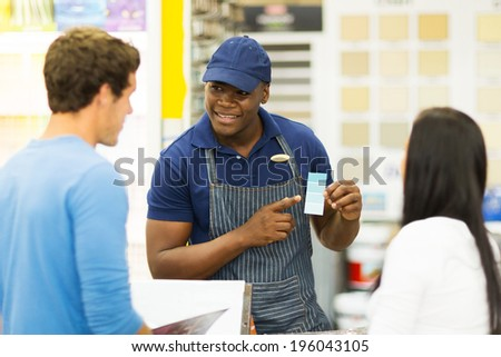 african paint store salesman helping couple choosing paint color - stock photo