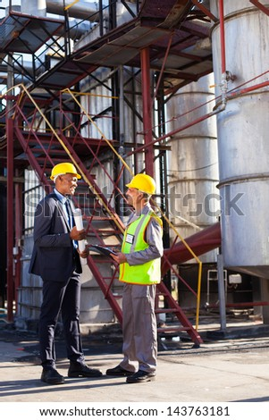 african petrochemical manager in discussion with plant worker outdoor - stock photo